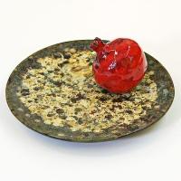 Гранат на керамическом блюде